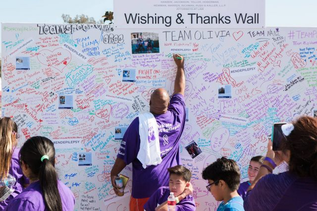 People signing wishing and thanks wall full of stories