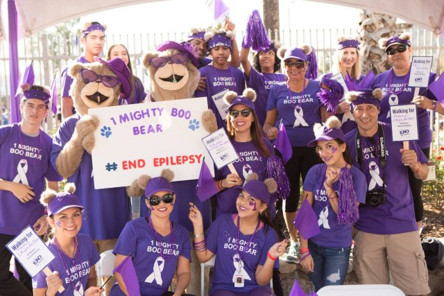 Group dressed in purple with signs