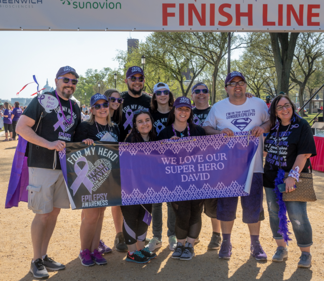 Group at finish line with sign