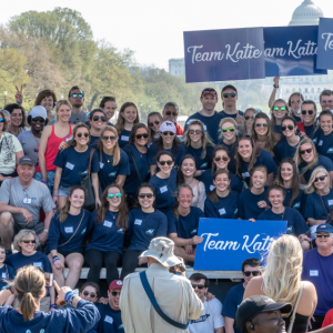 "Large group at a walk with signs ""Team Katie"""