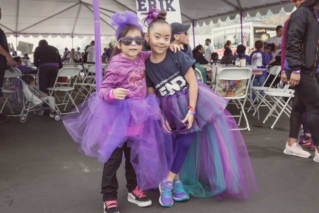 Tow girls with purple shirts and dresses posing together