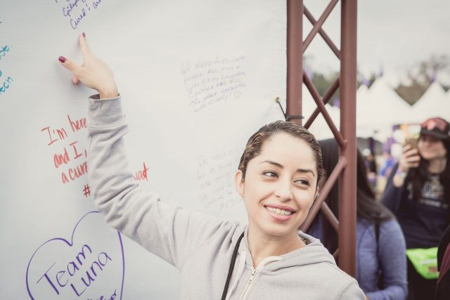 Girl pointing to her signature on signing board