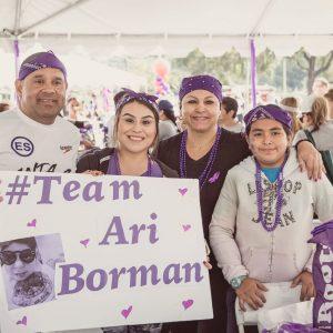 "Group holding sign ""Team Ari Borman"""